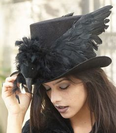 haunted raven top hat - A creepy black raven nests on the brim of this black top hat. Pair the topper with a black cloak for an easy, yet eerie, Halloween ensemble.