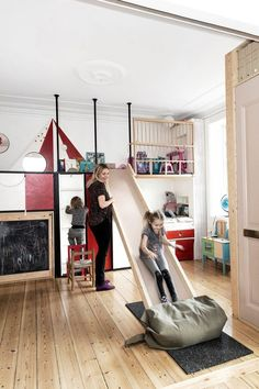 The built-in wood unit takes up the entire facing wall, concealing within itself not only nooks for the children to play in but also their beds, closet space for clothes and toy storage. This space is also the playroom and has many fun elements: a blackboard, removable bed slide or hidden desk.