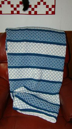 Delicate shades of blue and white combine with slip stitches to create an embroidered look on a heavenly throw