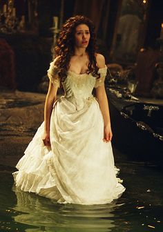 Phantom of the opera  Christine Daae is supposed to be a figure of innocence throughout the film and as such her dresses reflect this. This dress is fitted and sophisticated but is white and therefore a colour connected with being virtuous. I love the cut and draped skirt on this dress especially in the way it reflect the ripples in the water.