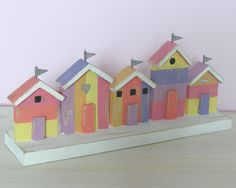 Bright Coloured Wooden Beach Huts by Shoeless Joe