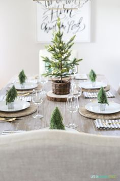 A neutral Christmas dining room with a navy blue striped rug, linen chairs, reclaimed wood dining table, large 'O Come Let Us Adore Him' canvas art, flocked Christmas tree, a seagrass tree collar, Darlana linear pendant light fixture and woodland coastal decor. #christmasdecorations #christmasdecor #christmasdiningroom #diningroom