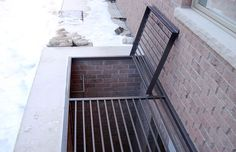 A custom wrought window well cover with an emergency ladder inside and an opening hatch.