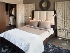 Upholstered folding privacy screens on both sides of the bed are used to add texture and dimension to the bedroom.