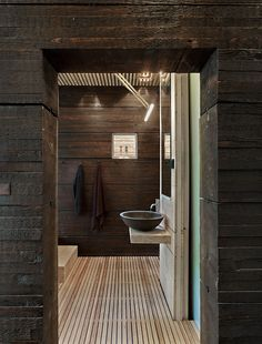 Swedish guesthouse bathroom with pine walls covered in tar and a Vola faucet