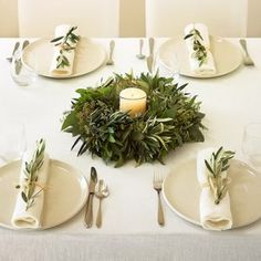 This is like our table. Olive branch wreath with bits of rosemary, candles with rosemary sprig. A little sprig of rosemary on the plates