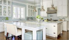 White kitchen with blue/grey butcher (subway) tile, timber floor, bench and drum seating, industrial lighting - lots to admire