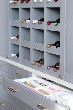Amazing kitchen boasts a gray built-in wine rack stacked over gray drawers filled with party accessories.