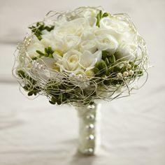 The FTD® Evermore™ Bouquet White roses, spray roses, freesia, and hydrangea are accented with green hypericum berries and presented in an elegant gold wire bouquet collar displaying ivory pearls. With the stems wrapped in an ivory satin ribbon accented with domed silver buttons... no wire collar though