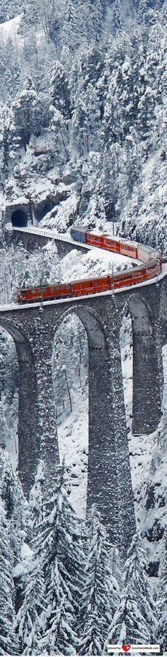 Wonderful red train on a bridge in the forest with snow all around.