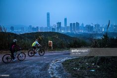 People cycles at Kwu Tong with backdrop of Shenzhen on April 1, 2016 in Hong Kong. Despite recent protests seen from Hong Kong's opposition lawmakers on the construction of a high-speed rail linking the city to Shenzhen and Guangzhou, Hong Kong's future has been increasingly dependent on China's megacities across the border. Also known for being the global hub for China, Hong Kong's economic role in the region faces further challenges as its neighbouring mainland cities continue to grow…
