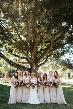 the bride with her bridesmaids in neutral gowns pose under an ancient oak tree before heading into the church holding their loose and unstructured bouquets of burgundy, ivory, white and peach flowers.
