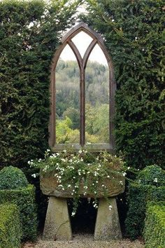 Is it a mirror or a window? Lovely garden design with stone planter.
