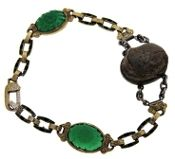 20th Century circa 1920 - Art Deco era.  Estate Krementz Diana, Egyptian Revival bracelet featuring a center glazed faience scarab set in silver accented by 2 dyed gree Chalcedony floral carved cabochons with a 14kt yellow gold engraved links.  The bracelet is finished with green and black enameling and a lobster claw clasp.