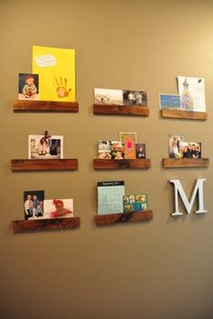 Use flat strips of wood, and attach with hotglue to the wall to create a gap to slide cards/photos/art into