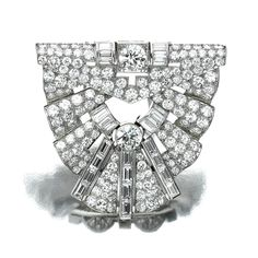 DIAMOND CLIP, 1930S.  Of geometric design, set with circular-cut and baguette diamonds.