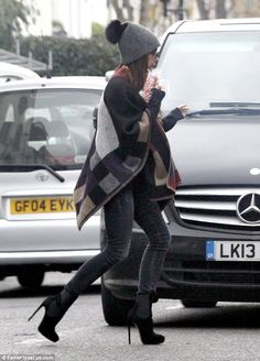 Bundled up: Victoria Beckham stepped out in London on Tuesday, rocking a Burberry blanket poncho, figure-hugging skinny jeans and a rather fun woolly bobble hat Poppy Delevingne, Sienna Miller, Alexa Chung, Burberry Poncho, Burberry Plaid, Burberry Prorsum, Victoria Beckham Stil, Blanket Poncho, Grey Skinny Jeans