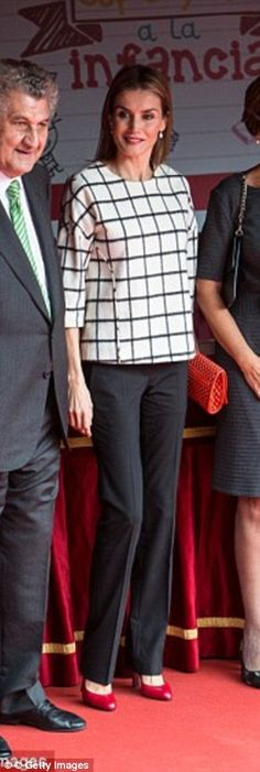 Queen Letizia pictured in October 2014 when she manned a Red Cross stall in Madrid wearing the same Designers Remix top she would later wear to events in November 2014 and February 2015.