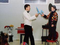 Goochelaar Aarnoud Agricola geeft een assistent uit het publiek een ballondier dat hij heeft gemaakt van een modelleerballon tijdens het voorprogramma van een sinterklaasfeest bij een bedrijf in Apeldoorn in het begin van de jaren '90.