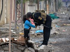 A member of Iraqi special forces kisses a child in