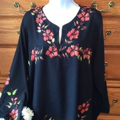 """Island Planet Black Floral Boho Tunic 100% rayon and in very good condition.  Black embroidery around the flowers and leaves.  Green leaves and a sort of salmon, orange color to the flowers.  28"""" in length and when laid flat it is 22"""" across measured armpit to armpit.  It then gradually increases in measurement until the bottom hem which has slits to 25"""" across.  The tag size says ONE SIZE.  To me it is equivalent to an XL.  Quick iron touch up.  Light weight material and comfy.    Slits at…"""