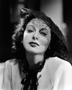"""Alluring shadows are cast by the black lace of this formal hat designed by Irene for Hedy Lamarr to wear in The Heavenly Body"". 1944"