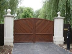 large aluminium timber effect driveway gates installed on driveway with stone columns