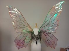 These are extra large fairy wings made with a very lightweight cut aluminum sheet and a laminated iridescent film that reflects a rainbow of colors. The green pair shown in the photos has a slightly different butterfly shaped frame but it is an example of the color pattern available. The wings in this listing have black veins rather than the copper shown in the first 4 photos.