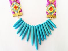 Now available on AHALife - Shh by Sadie handmade statement necklace. Hand beaded seed bead Aztec straps with bright turquoise spikes. Fashion / style / jewellery / jewelry / handmade / artisan / bespoke