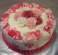 Hearts and Flowers - Red, white, and pink buttercreme roses, surrounded by oodles of royal icing Valentine hearts, also in red, white, and pink. I made some of them solid and some of them swirly heart outlines. I was very pleased with the result!