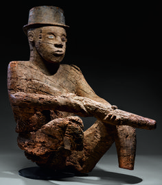 https://www.vogue.com Hélène Leloup on Mbembe Sculpture, the Rare African Art Now at the Met Seated Male Figure with Rifle and Bowler Hat - Mbembe peoples; Ewayon River region, Cross River Province, Nigeria
