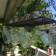 DIY mason jars hung on a pot rack. Fill with candles or twinkle lights. Sweet smelling pots of mint drape over the side.