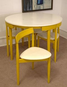 An ingeniously space-saving midcentury dining table and chairs - the curve of the chair back fits perfectly against the table edge! Love the rounded triangular seat and the yellow and white color scheme.