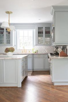 White and gray kitchen designed with light gray cabinets, marble countertops and a brass faucet under a window. White and gray kitchen designed with light gray cabinets, marble countertops and a brass faucet under a window. Blue Gray Kitchen Cabinets, Light Gray Cabinets, Grey Kitchen Island, Gray And White Kitchen, White Kitchen Decor, Painting Kitchen Cabinets, Kitchen Ideas, Kitchen Reno, Gray Island