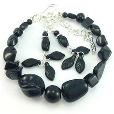 Komplet biżuteriidamskiej wykonany ręcznie. Kolczyki i bransoletkaz czarnych koralików szklanych jablonex i elementów w kolorze srebrnym. Kolczyki w kształcie listków.