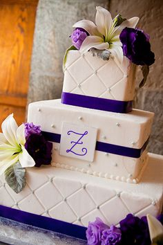 Purple wedding cake topped with lilies