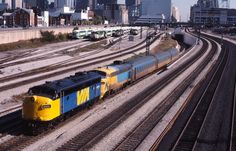 Caption: 121 departs Toronto with a VIA leader Photographer: John Eull Date: Via Rail, Electric Train, Train Engines, Long Distance, Locomotive, Caption, Ontario, Airplane, 1980s