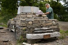 """Chris Miller works on the final day of construction on a stone truck he has built on the roadside in Maple Corner Vermont. The concept for the creation is based on the """"rusty old farm trucks"""" that """"every little town in Vermont is blessed with""""."""