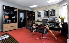 Executive office with custom designed wall unit. Oak veneer, black lacquer and tinted frameless glass doors.