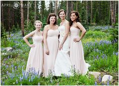 Bridesmaids wearing long light pink bridesmaids dresses stand in a field of pretty purple wildflowers on a wedding day in Breckenridge, Colorado.  This nice wooded area with wildflowers is located in a neighborhood at the end of White Cloud Drive near Carter Gulch. - April O'Hare Photography http://www.apriloharephotography.com #Breckenridge #Colorado #ColoradoWedding #BreckenridgeWedding #BreckWedding #PurpleWildflowers