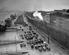 This photo shows cars parked on the cobblestone levee in front of the future Arch grounds in May 1938. At right, a switching locomotive hauls boxcars along the riverfront railroad trestle. Owned by the Terminal Railroad Association, the trestle wasn't removed until the early 1960s, when the track was rerouted on the tunnels and cuts running through the Jefferson National Expansion Memorial. Moving those tracks proved to be one of the major sources of delay for the project. (Post-Dispatch)