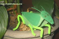 grasshopper, cut toilet paper tube in downward slant, hot glue pipe cleaners and add wings