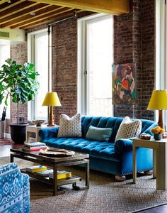 Yellow and blue living room features exposed brick walls and yellow beamed ceiling over turquoise velvet tufted sofa with rolled-arms flanked by end tables topped with table lamps with yellow lamp shades across from Greek key coffee table.