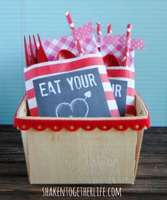 Party pouches tucked in a berry basket at the end of a buffet line - great idea! No more lost napkins or dropped silverware! FREE printable tags, too.
