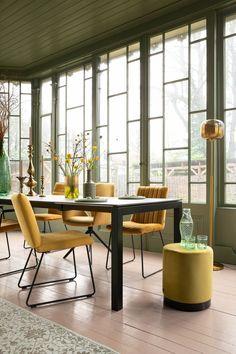 Creëer in jouw eethoek een zonnige sfeer met gele eetkamerstoelen. Wil je niet alle stoelen in hetzelfde design? Mix en match dan verschillende soorten in dezelfde kleur. Voor nog meer warmte in je eethoek kan je kiezen voor velvet eetkamerstoelen Deze zijn niet alleen mooi om naar te kijken, ze zitten ook nog eens heerlijk zacht en comfortabel. Maak het geheel af met gele accessoires. | velvet eetkamerstoel | okergele stoel | okergeel interieur | gele eethoek | eetkamerstoel geel Dining Chairs, Dining Room, Dining Table, Living Room Green, Modern Design, Interior, Furniture, Brunch, Conservatories