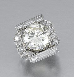 DIAMOND RING, 1930S.  Centring on a circular-cut diamond weighing 7.28 carats, within a rectangular plaque set with baguette and triangular diamonds, the shoulders pierced and millegrain-set with circular-cut stones, to a scrolled gallery highlighted with single-cut diamonds, size I½, inscribed to inside of band 25-V-35.