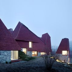 Rooms topped with chimney-like roofs surround a secluded courtyard to from this house in Kent, England, which takes its angular form and russet colouring from the area's hop-drying oast towers.