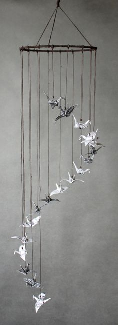 I created this cheerful and comforting mobile inspired by Japanese minimalism. Cranes are Japanese symbols of happiness and fulfillment of dreams. This mobile is made using 18 origami cranes folded from acid and lignin free paper, beads and strings. Everything is carefully handmade with true tenderness. Ready-to-hang, doesn't need to be assembled.  Here are its dimensions: Diameter: 18 cm Height: 76 cm  Origami cranes create a spiral flying up into the sky.  The idea of each mobile arises…