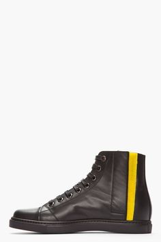 MARC JACOBS //  Black Leather Velcro-Trimmed High-Top Sneakers  32190M050006  High-top leather sneakers in black. Round toe. Black lace up closure with gunmetal tone eyelets. Velcro closure at inner and outer sides in yellow. Perforated logo code at closure and tongue. Textured black rubber foxing. Tonal stitching. Leather upper, rubber sole. Made in Italy.  $730 CAD
