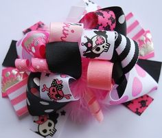 This bow is created in princess pirate colors - hot pink, black and white .. with skulls, tiaras, and princess ribbon too ..layered with ribbon, korkers,